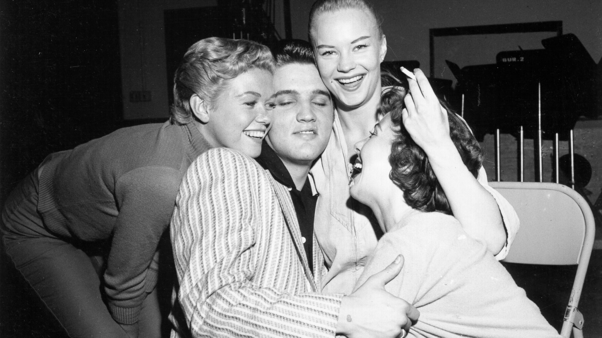 Rock and roll musician Elvis Presley gets mobbed by girls backstage of the Milton Berle Show in Burbank, California, 1956. (Credit: Michael Ochs Archives/Getty Images)