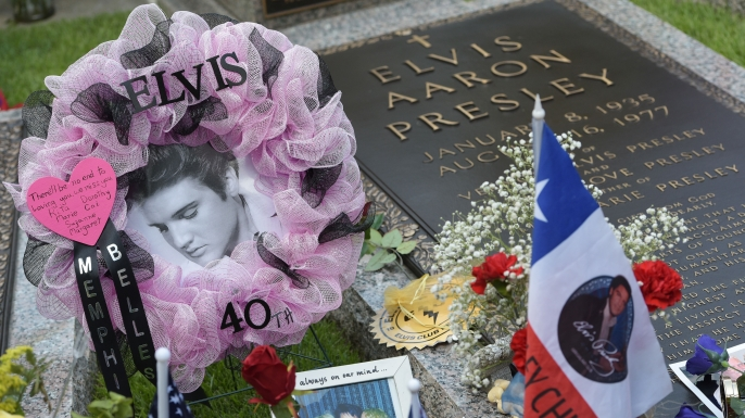 Tributes and momentoes are seen next to the marker for Elvis Presley in the Meditation Garden where he is buried alongside his parents and grandmother at his Graceland mansion in August 2017, the 40th anniversary of his death. (Credit: Mandel Ngan/AFP/Getty Images)