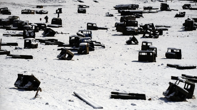 Afghan men walk amongst the remains of Russian military vehicles on the outskirts of Kabul on February 14, 2009 on the eve of the 20th anniversary of the withdrawal of Soviet troops from Afghanistan.  Soviet troops withdrew from Afghanistan on February 15, 1989, after ten years of fighting against Mujahiddin millitamen. (Credit: Massoud Hossaini/AFP/Getty Images)