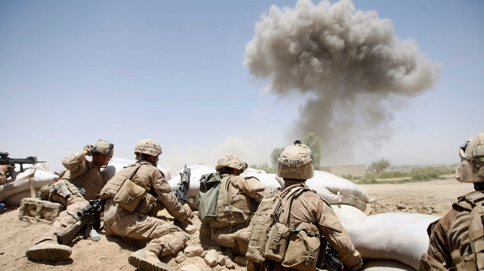 U.S. Marines from 2nd Marine Expeditionary Brigade, RCT 2nd Battalion 8th Marines Echo Co. take cover as a 500 lb bomb explodes on a compound after the Marines took two days of enemy fire from the position in Main Poshteh, Afghanistan, 2009. (Credit: Joe Raedle/Getty Images)