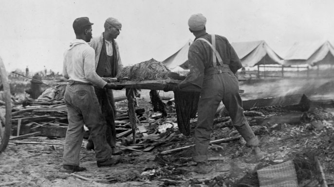 Men carrying a body on a stretcher, surrounded by wreckage of the hurricane and flood in Galveston, Texas, 1900. (Credit: Buyenlarge/Getty Images)