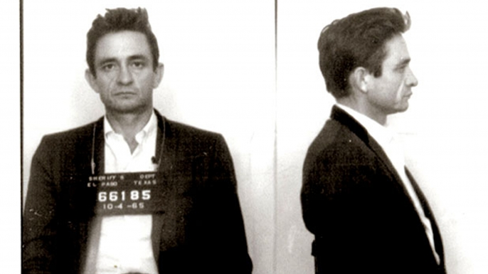 Johnny Cash poses for a mug shot after U.S. Customs agents found hundreds of pep pills & tranquilizers in his luggage as he returned from Mexico in October 1965. (Credit: Michael Ochs Archives/Getty Images)