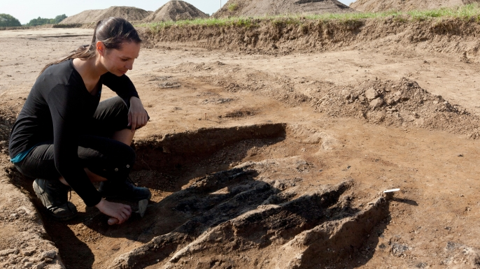 Nanna Holm, Chief Curator at the Danish Castle Center, working on excavated remains from burned wooden pillars which was part of the Northern gate in this newly found Viking Ring Castle, 2014. (Credit: OJPHOTOS/Alamy Stock Photo)