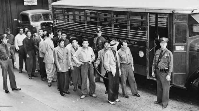 Zoot suiters lined up outside Los Angeles jail en route to court after feud with sailors, 1943. (Credit: The Library of Congress)