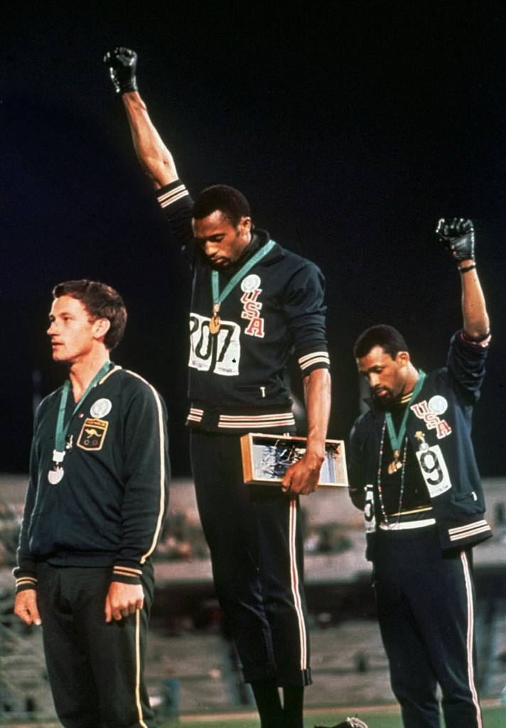 U.S. athletes Tommie Smith, center, and John Carlos raise gloved hands skyward during the playing of the Star Spangled Banner after Smith received the gold and Carlos the bronze for the 200 meter run at the Summer Olympic Games in Mexico City, 1968. (Credit: AP Photo)