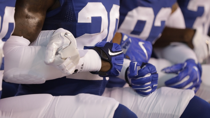 Members of the Indianapolis Colts lock arms as they take a knee during the Nation Anthem before an NFL football game against the Cleveland Browns in Indianapolis, September 24, 2017. (Credit: Darron Cummings/AP Photo)