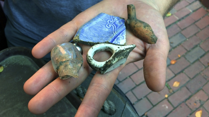 Boston city archaeologist Joe Bagley displays fragments of pottery and a tobacco pipe recovered from a site that experts believe may have contained an outhouse used by Paul Revere, September 28, 2017. (Credit: William J. Kole/AP Photo)