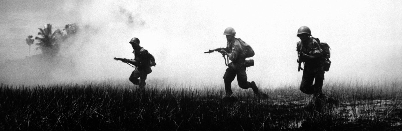 Troops  running across marshy terrain in Vietnam's delta country, during operations against the Communist Viet Cong guerillas. (Credit: Interim Archives/Getty Images)