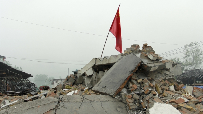 A Chinese flag on ruins of damaged houses in Longmen township, one of the seriously-damaged towns in disaster hit Yaan, southwest China's Sichuan province, April 2013. (Credit: STR/AFP/Getty Images)