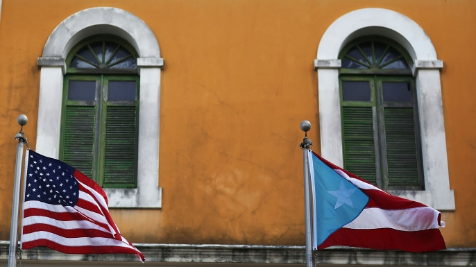 An American flag and Puerto Rican flag fly next to each other in Old San Juan a day after the Puerto Rican Governor Alejandro Garcia Padilla gave a televised speech regarding the governments $72 billion debt in San Juan Puerto Rico 2015. (Credit Joe R
