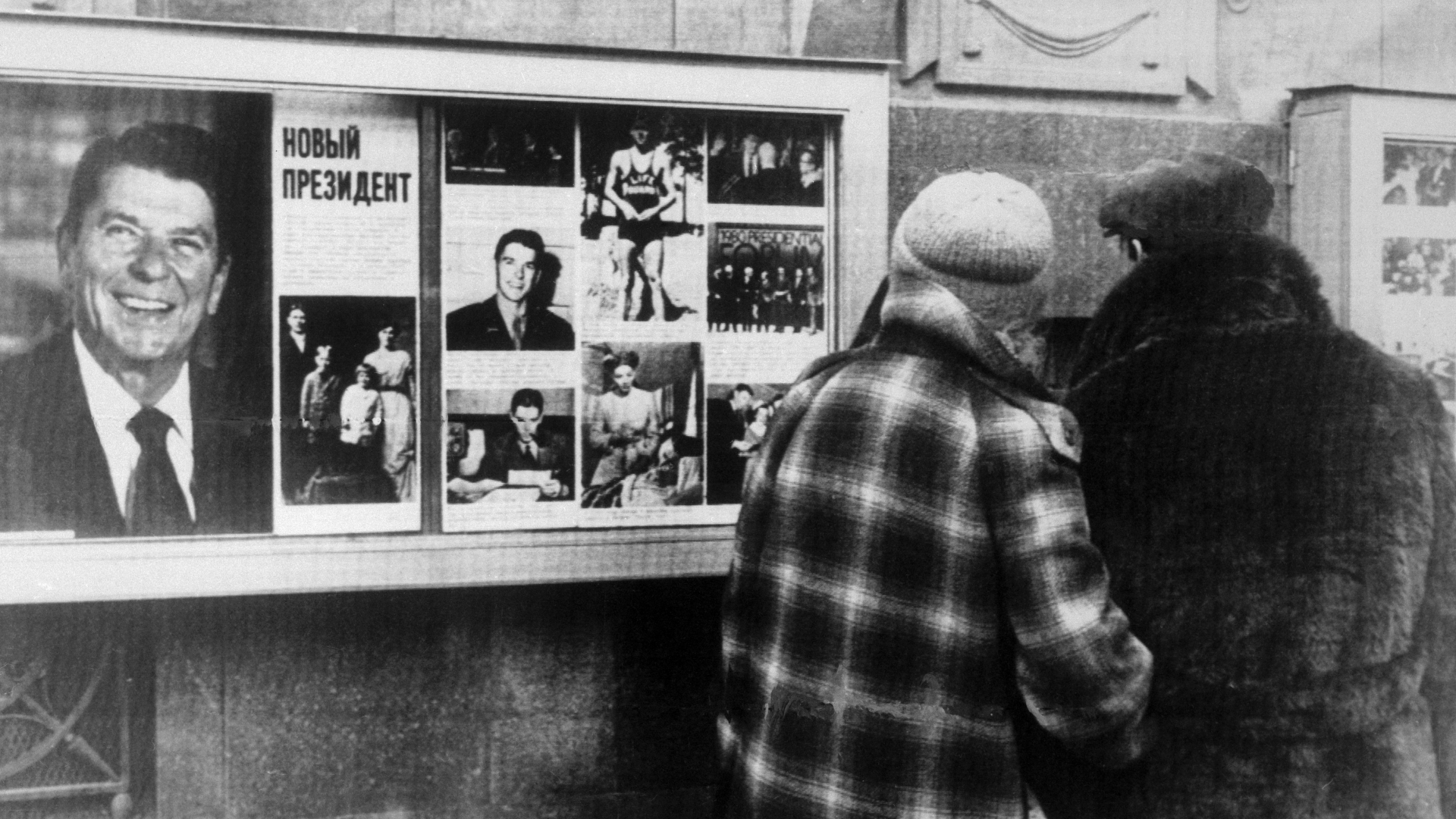 Muscovites stop and glance at a display of photographs of President-Elect Ronald Reagan on outside wall of the U.S. Embassy. (credit: Bettmann/Getty Images)