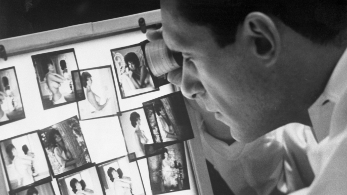 Hefner reviewing photographs in his Chicago office. (Credit: Bettmann/Getty Images)