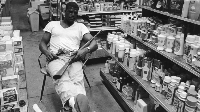 Heavyweight boxer Amos Lincoln, aka Big Train, guards the family drug store during rioting in the Watts area of Los Angeles, 1965. (Credit: Express/Archive Photos/Getty Images)