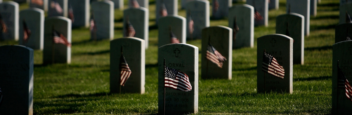 Small US flags are placed in front of headstones at Arlington National Cemetery during the Flag-In Ceremony ahead of the Memorial Day weekend, 2007 . It took approximately 3 hours for 1,300 soldiers, sailors and marines to put more than 300,000 flags in front of each of the gravestones at Arlington National Cemetery. (Credit: Chip Somodevilla/Getty Images)