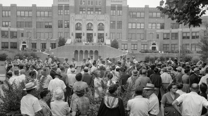 The crowd gathered outside Little Rock Central High School. The military men were ordered by Governor Orval Faubus to surround the school and prevent Black students from entering the grounds. (Credit: William P Straeter/AP/REX/Shutterstock)