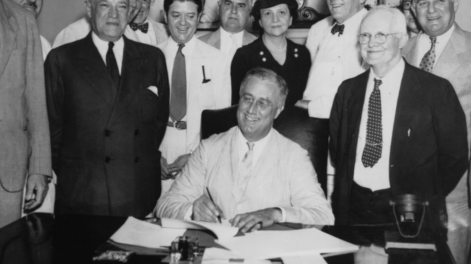 President Franklin D. Roosevelt signs the Social Security Act on 14th August 1935. From left to right, Robert Lee Doughton, chairman of the House Ways and Means Committee, Edwin E. Witte, Director of the President's Social Security Committee, with Senator Robert F. Wagner, co-author of the bill behind him, Senator Robert La Follette, Senator Augustine Lonergan, Labor Secretary Frances Perkins, Senator William H. King, Rep. David John Lewis, co-author of the bill and Senator Joseph F. Guffey.