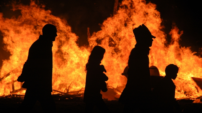 A family is silhouetted by a bonfire on Halloween night.