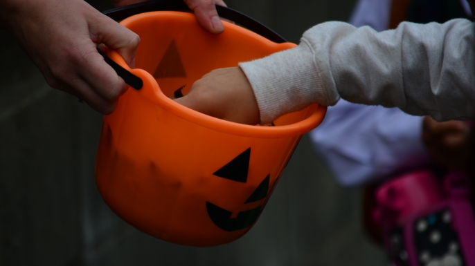 Child's hand picking candy from a Halloween basket