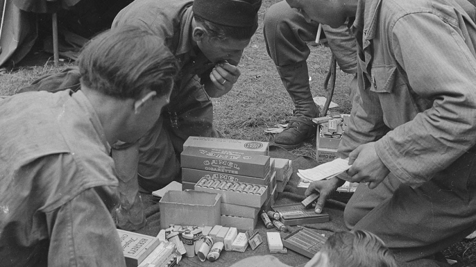 U.S. soldiers with cigarette and food rations during World War II