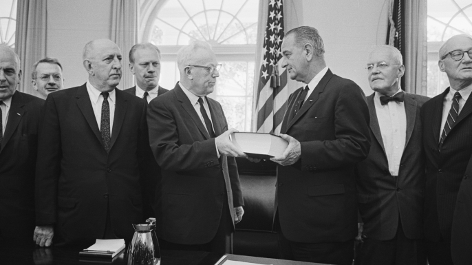 Chief Justice Earl Warren hands over his report on the Kennedy assassination to President Johnson. The lengthy report, submitted on September 24, 1964, was composed by the seven-member panel who investigated the murder. (Credit: Bettmann/Getty Images)