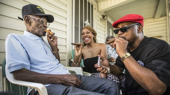 Richard Overton smoking a cigar with a few neighborhood friends Donna Shorts and Martin Wilford in Austin, Texas, 2015. (Credit: Ricardo B. Brazziell/Austin American-Statesman via AP)