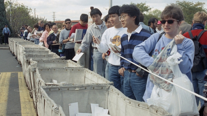 People placing visa applications in bins outside the Merrifield, Virginia post office in hopes of receiving one of the 40,000 green cards to be distributed via lottery on a first-come, first-served basis, 1991. (Credit: Robert Brown/AP Photo)