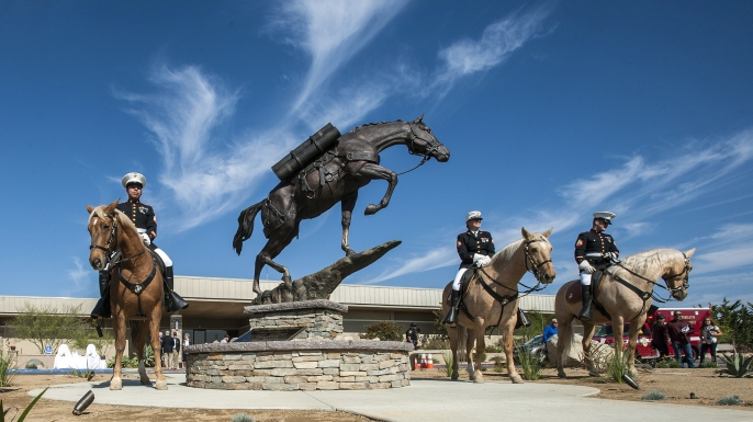 The Marine Corps Mounted Color Guard poses for photographs with the bronze statue of Staff Sergeant Reckless, a horse that served in the Korean War from Camp Pendleton, following a dedication ceremony at Camp Pendleton, 2016. (Credit: Mark Rightmire/The Orange County Register/SCNG via AP)
