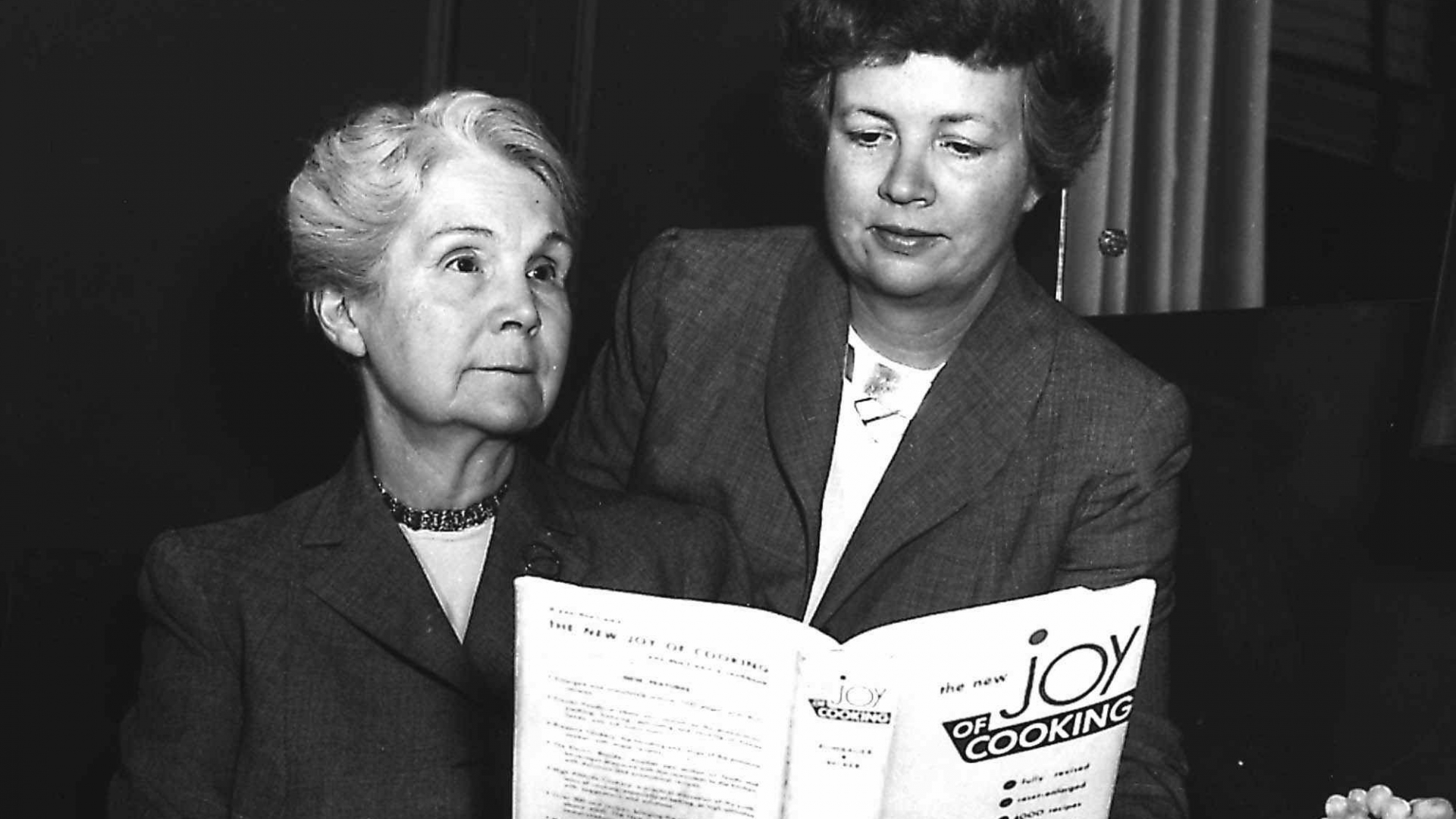 """Marion Rombauer Becker (right) looks over the """"Joy of Cooking"""" with her mother Irma Rombauer, in this 1951 photo. (Credit: AP Photo)"""