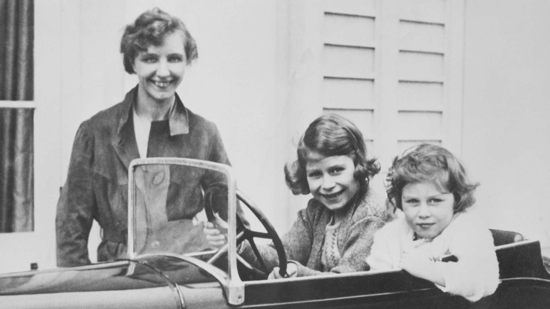 Princess Elizabeth (center) and her younger sister Princess Margaret of Great Britain play in a miniature automobile while their governess, Marion Crawford, keeps an eye on them. Elizabeth will grow up to become Queen Elizabeth II. (Credit: Bettmann Archive/Getty Images)