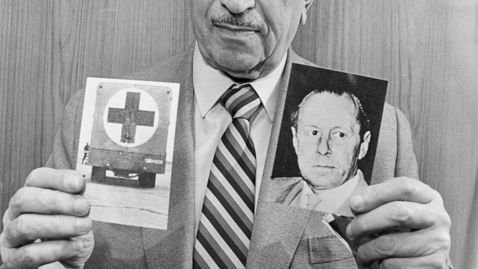 Nazi Hunter Simon Wiesenthal Holding Photographs Depicting Former Gestapo Chief Walter Rauff And A Mobile Gas