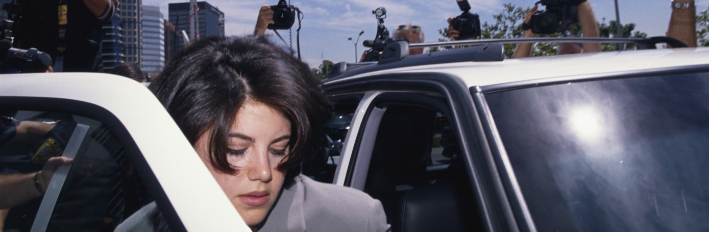 Monica Lewinsky surrounded by photographers as she gets into a car on her way to the FBI Headquarters. (Credit: Jeffrey Markowitz/Sygma via Getty Images)