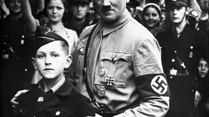 Nazi dictator Adolph Hitler posing with a young member of the Nazi Youth. (Credit: Corbis via Getty Images)