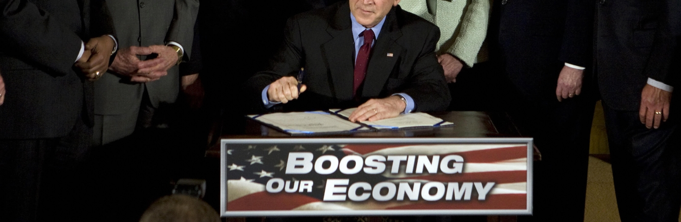 "US President George W. Bush (seated) flanked by Congress members and members of his cabinet signs the Economic Stimulus Act of 2008, on February 13, 2008 in the East Room of the White House in Washington, DC. Bush signed the two-year, 168-billion-USD stimulus package, praising it as ""a booster shot"" for the battered US economy. ""We have come together on a single mission, and that is to put the people's interest first,"" Bush said.  AFP PHOTO/Mandel NGAN (Photo credit should read MANDEL NGAN/AFP/Getty Images)"
