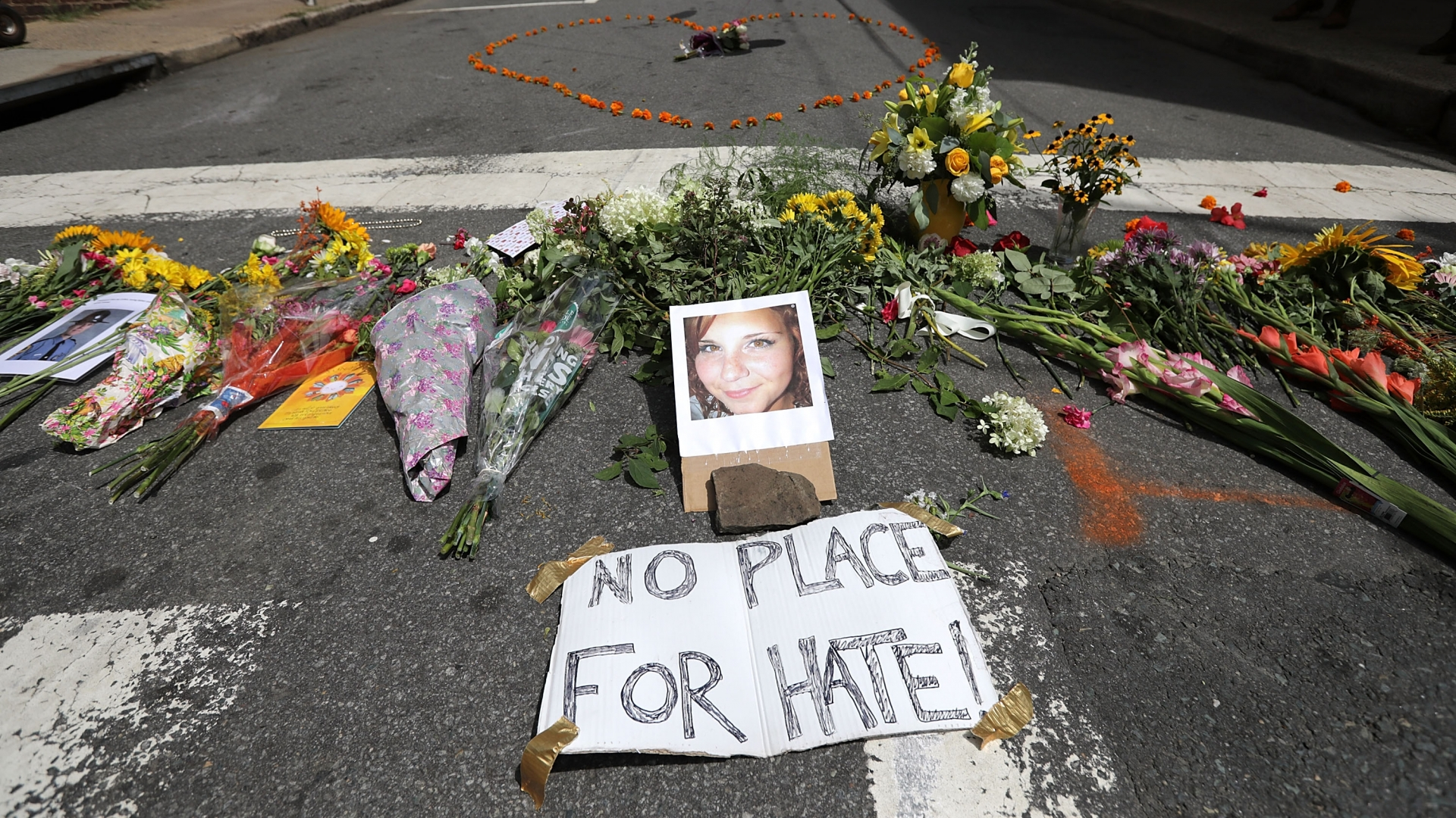 Flowers surrounding a photo of 32-year-old Heather Heyer, who was killed when a car plowed into a crowd of people protesting against the white supremacist Unite the Right rally, August 13, 2017 in Charlottesville, Virginia. (Credit: Chip Somodevilla/Getty Images)