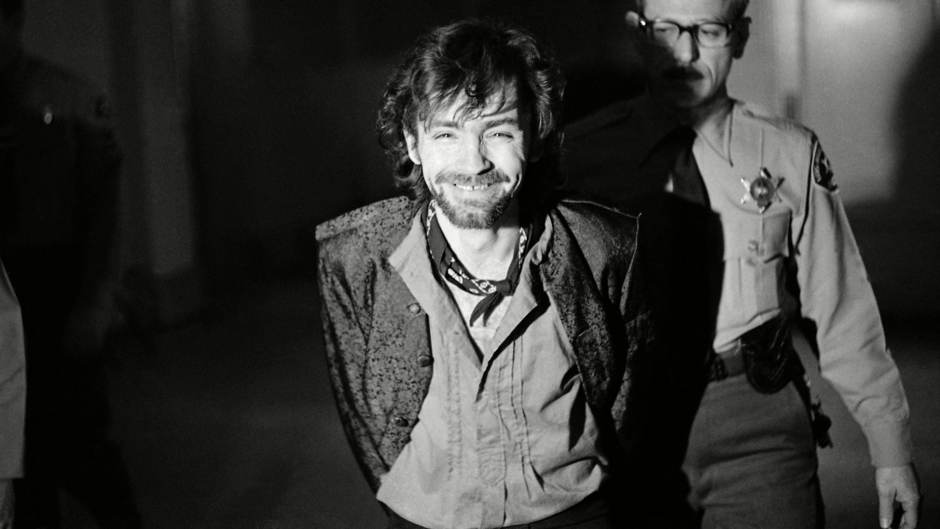 """A smiling Charles Manson during a break in the Tate murder trial after an outburst from his co-defendants. The trouble started after Leslie Van Houten said she wanted to fire her new lawyer, then slapped a bailiff and told the judge, """"I'd strike you if I could"""" before being ejected from the courtroom. (Credit: George Brich/AP/REX/Shutterstock)"""