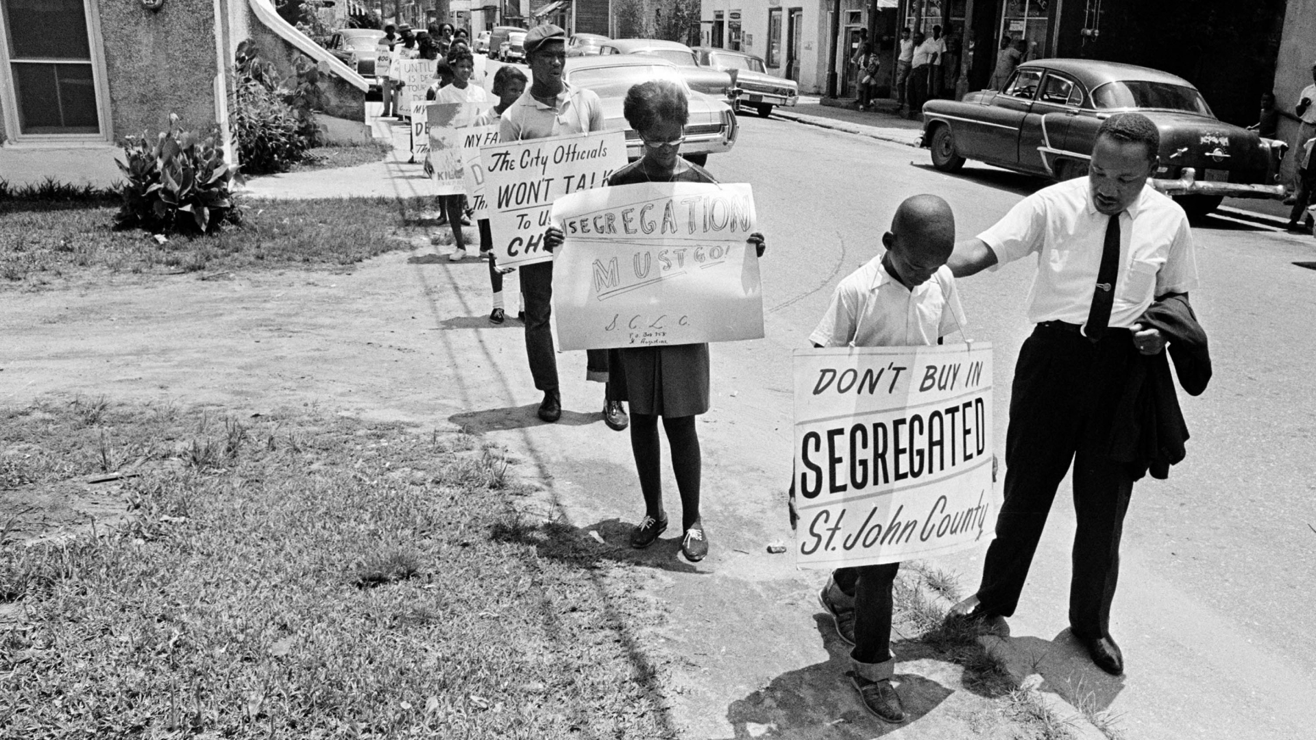 Dr. Martin Luther King, Jr. giving a young boy a pat on the back as a group of young people started to picket in St. Augustine, Florida, June 10, 1964. (Credit: AP Photo)