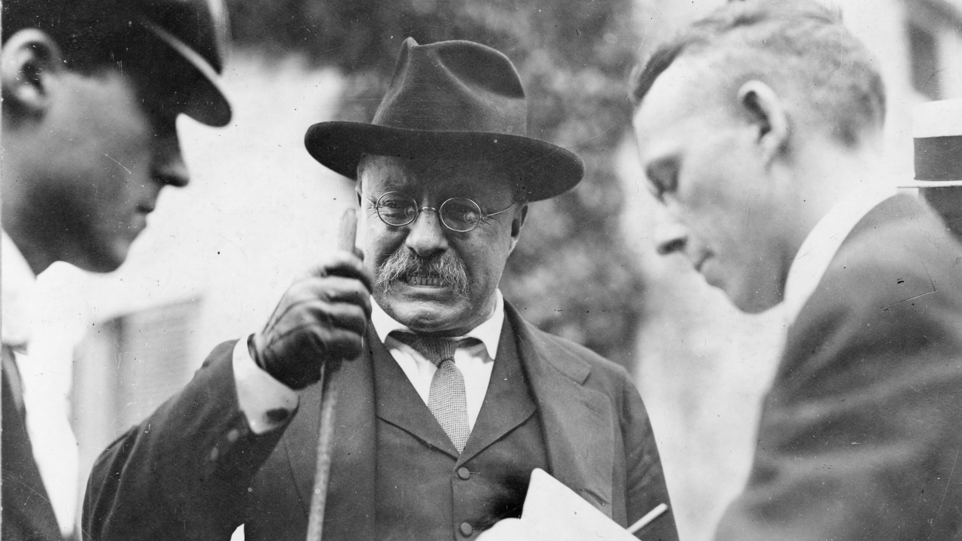 US President Theodore Roosevelt clenching his teeth as he makes a point during an interview with unidentified journalists. (Credit: PhotoQuest/Getty Images)