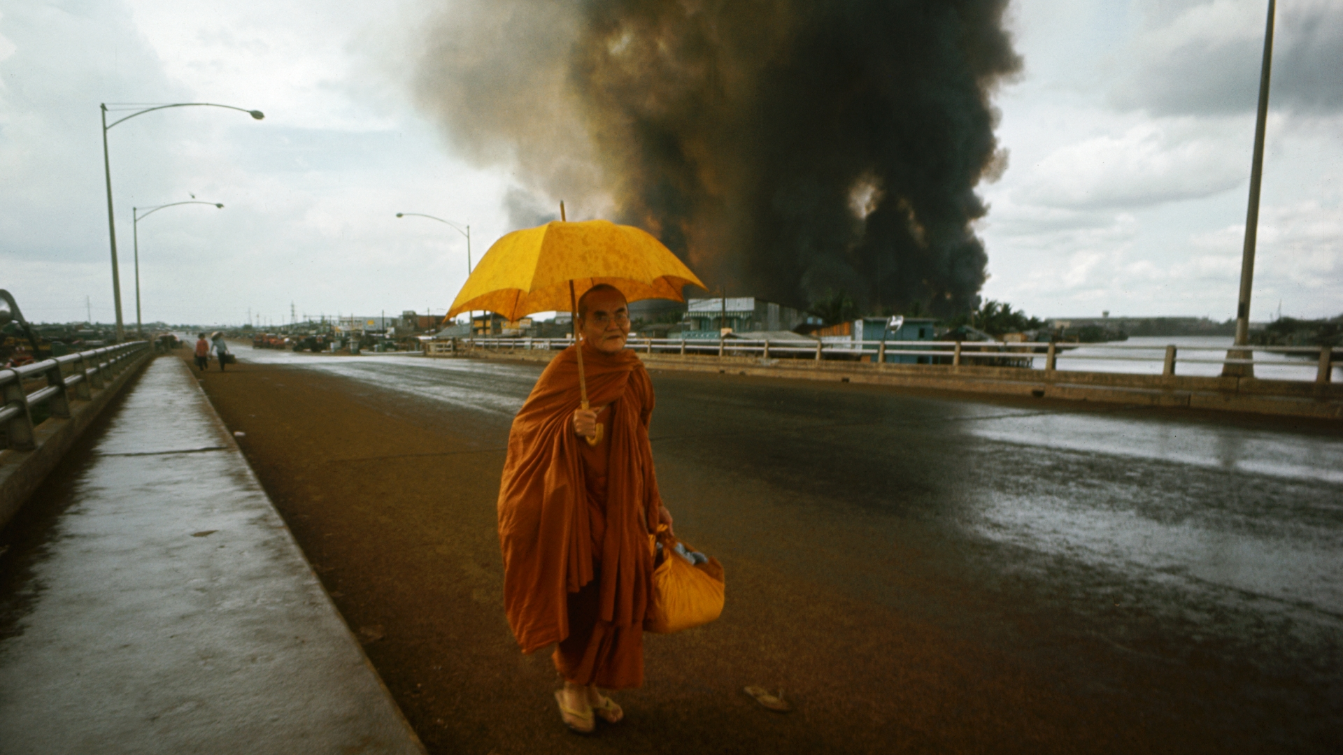 Fires burn behind a Buddhist monk crossing a bridge on the first day of the Tet Offensive. (Credit: Tim Page/CORBIS/Getty Images)