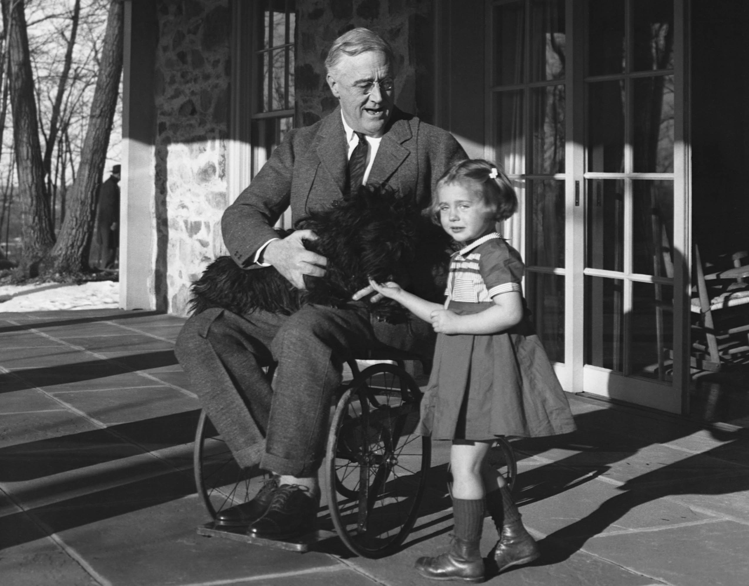 Franklin Roosevelt in his wheelchair with his dog and Ruthie Bie, the daughter of the Hyde Park caretaker. (Credit: Corbis via Getty Images)