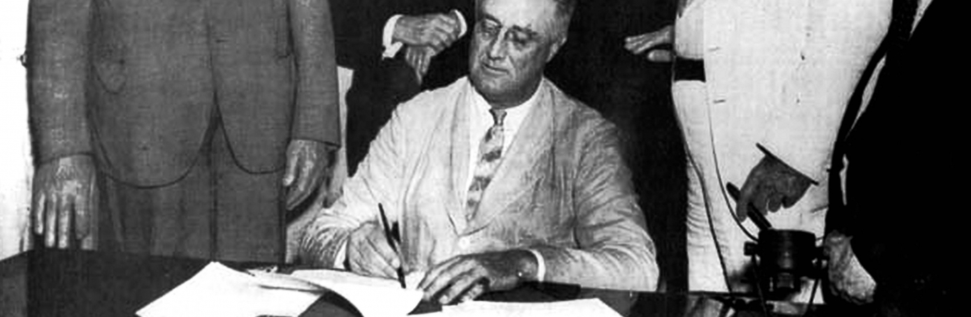 United States President Franklin D. Roosevelt signing the Social Security Bill (Act) in 1935. (Credit: Photo12/UIG via Getty Images)
