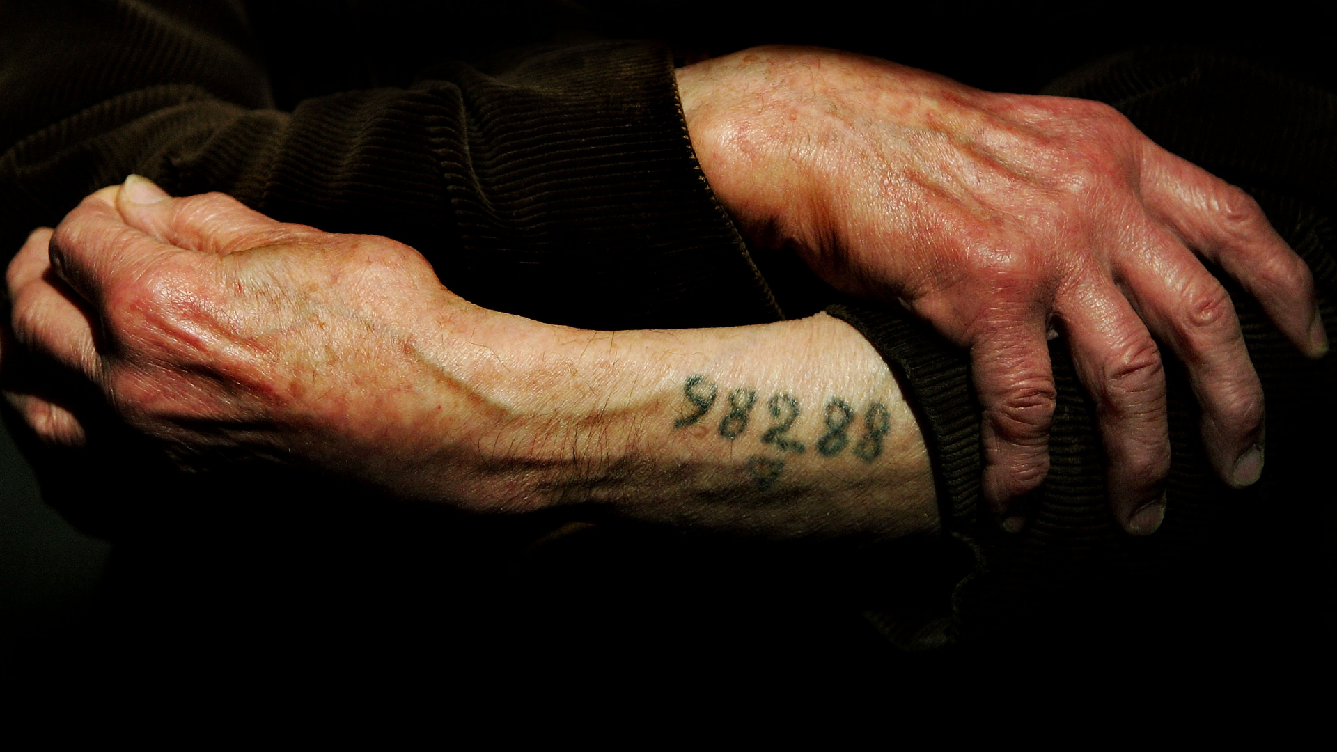 Auschwitz survivor Mr. Leon Greenman, displays his number tattoo at the Jewish Museum in London, England in 2004. (Credit: Ian Waldie/Getty Images)
