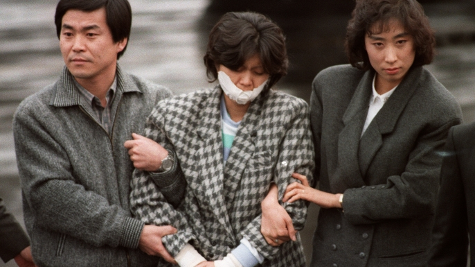 North Korean agent Kim Hyun-Hee, responsible for the Korean Air Flight 858 bombing in 1987 which killed 115 people, being escorted by South Korean investigators. (Credit: Sunkyu Im/AFP/Getty Images)
