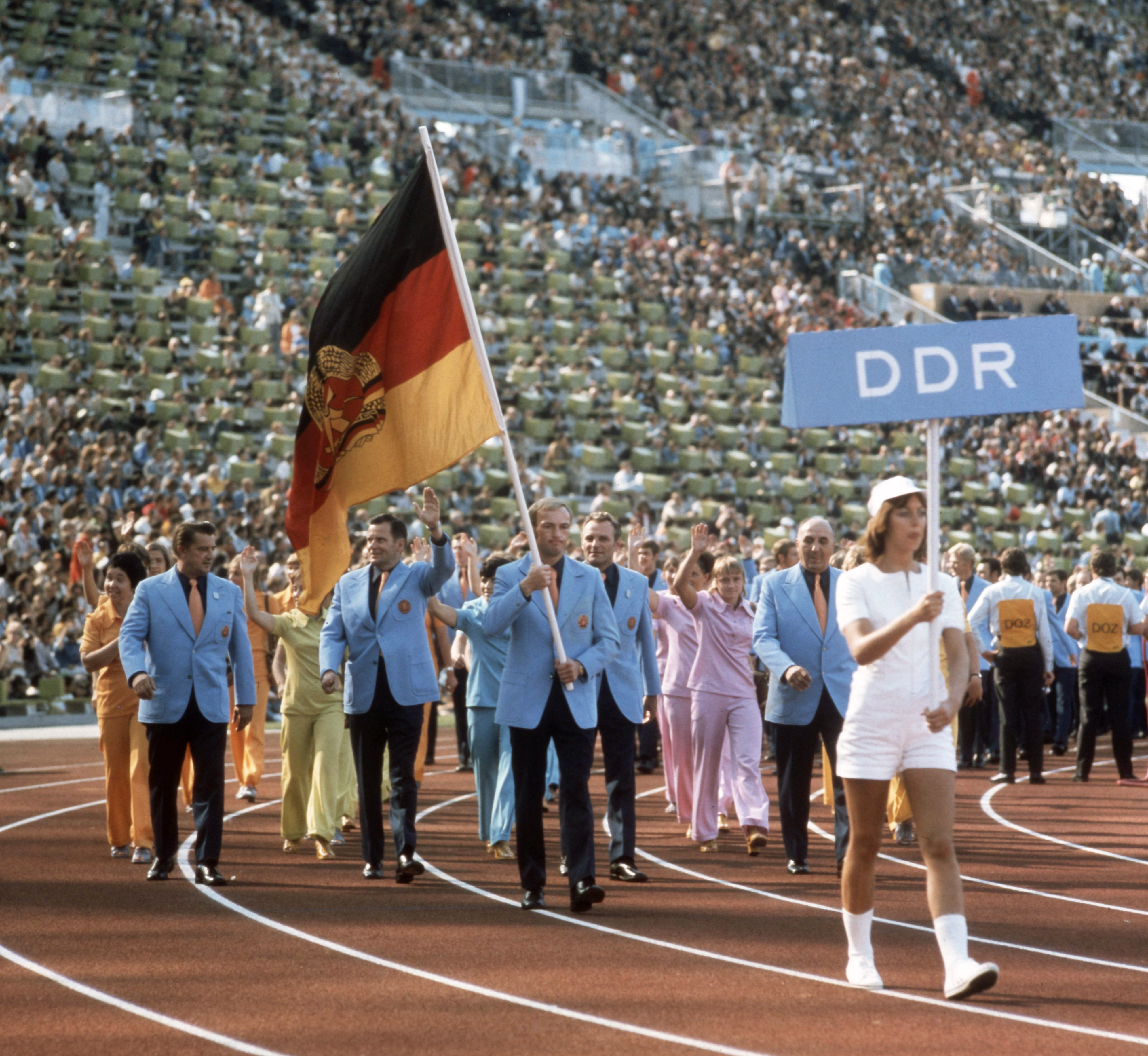The GDR  (German Democratic Republic) team holding the flag featuring the hammer and compass surrounded by a ring of rye. As a separate team, they marched with this version of the flag at the 1972 opening ceremony. (Credit: Werner Schulze/Ullstein Bild via Getty Images)