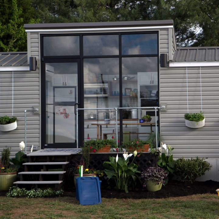Chelsea and Jeff's 172 square foot tiny house has floor to ceiling windows on one side to let in lots of light.