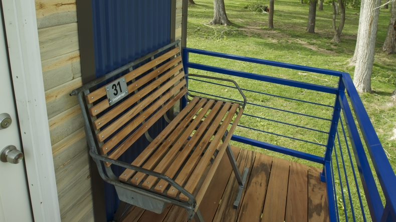 A chair lift serves as a bench on the back deck of the ski lodge tiny home.