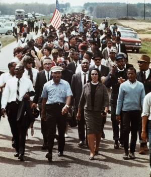 """Martin Luther King Jr, Coretta Scott King and John Lewis lead the march from Selma to Montgomery, several weeks after """"Bloody Sunday."""" (Credit: Corbis Images)"""