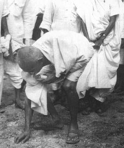 Gandhi picking up salt on the beach at Dandi on April 5, 1930.