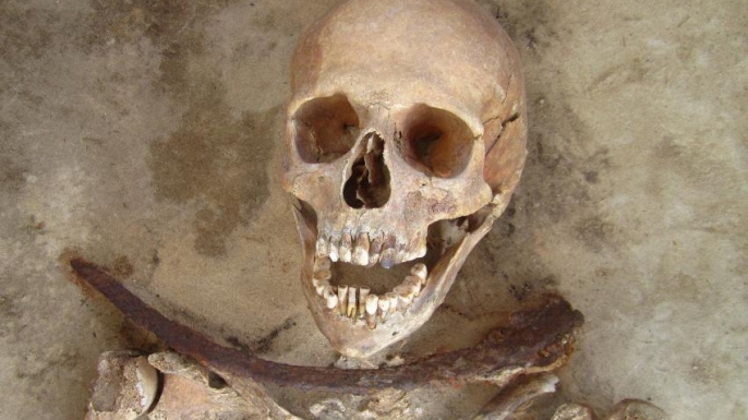 Female skeleton with sickle placed across her neck