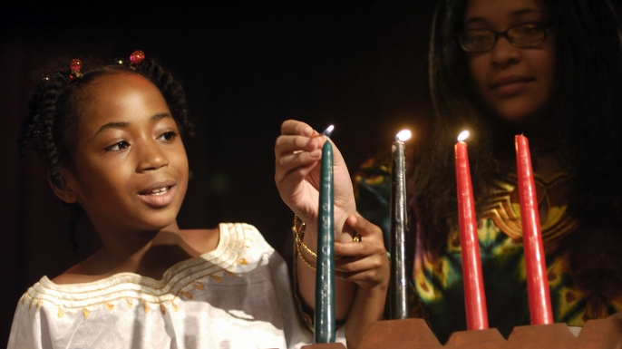 Brooklyn students light a candle celebrating Ujamaa.