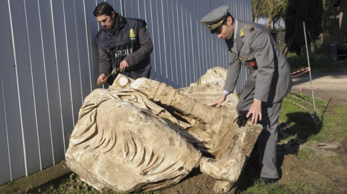 Italian officials inspect a statue thought to depict the emperor Caligula after recovering it from smugglers in January 2011.